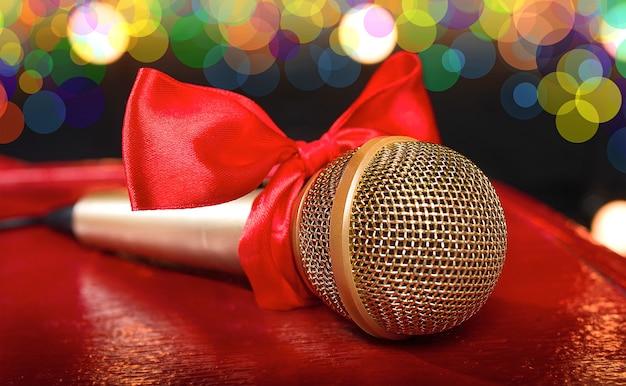 Золотой микрофон на красном деревянном и темном фоне с множеством огней