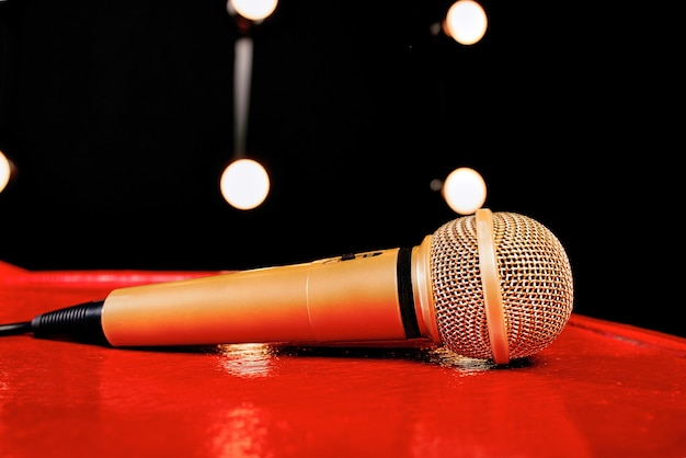 Gold microphone on red wooden and dark background with many lights