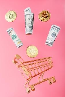 분홍색 표면에 공중 부양의 비행에서 비트 코인 동전과 미국 달러와 골드 미니 카트