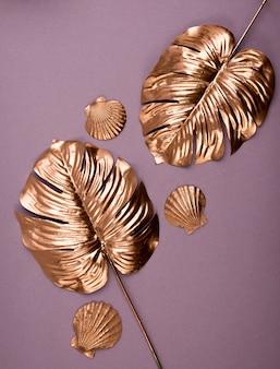 Золотые листья монстеры. вид сверху роскошных позолоченных тропических листьев.