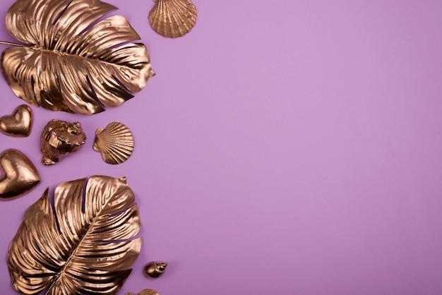 ゴールドモンステラの葉、貝殻、ゴールドハートコレクションフレームの上面図。