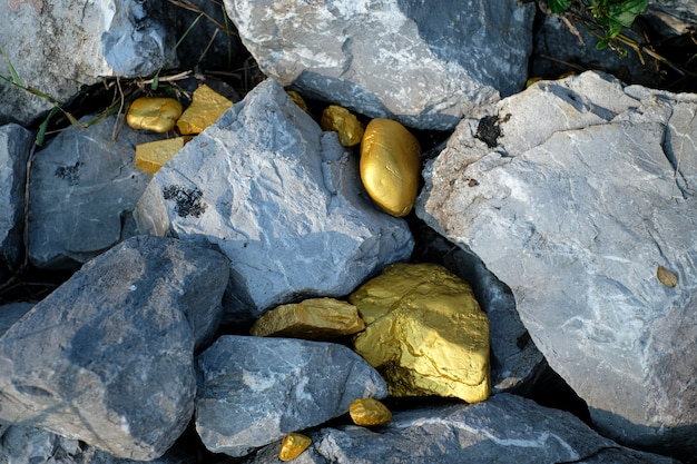 Gold nugget and grey granite stone background