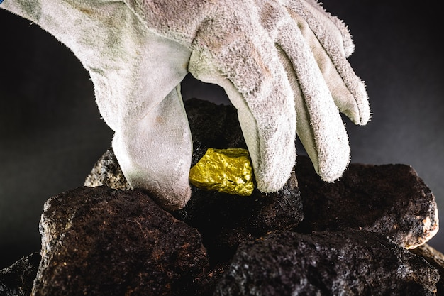 Золотой самородок в руке шахтера, скрытый золотой камень