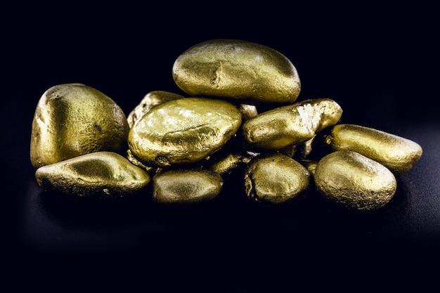 Крупный план золотых самородков изолированный на черной поверхности.