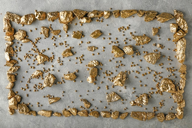 Gold nuggets on grey background