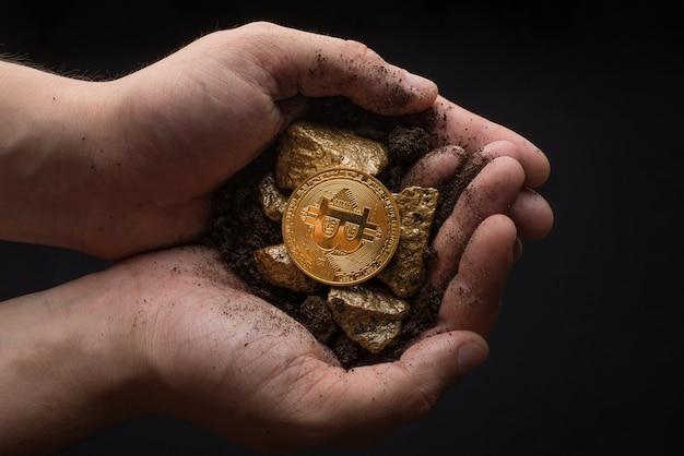 Золотые самородки с биткойном в руках майнера