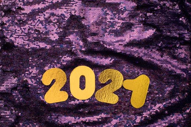 Золотые числа 2021 года на пайетках блестят на фиолетовом фоне.