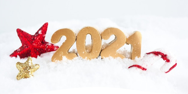 Золотые числа 2021 года, сверкающие красные и золотые звезды и леденец на снегу.