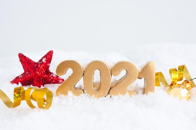 Золотые числа 2021 года, красная сияющая звезда и золотой серпантин на снегу.