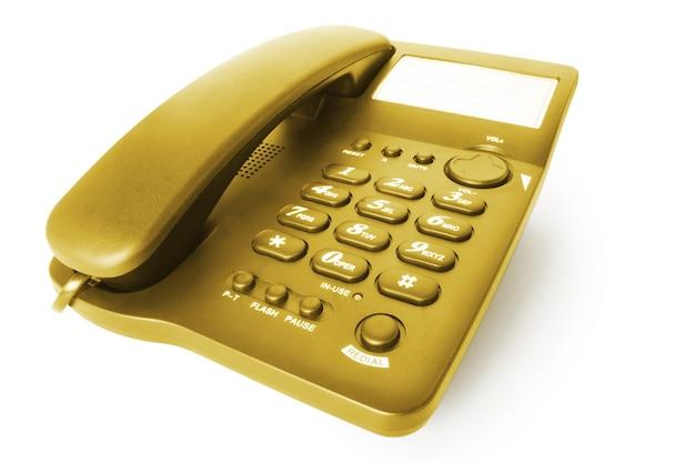 Золотой офисный телефон, изолированные на белом фоне