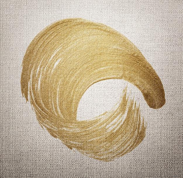 Текстура мазка кистью золотая масляная краска на текстурированном фоне коричневой ткани