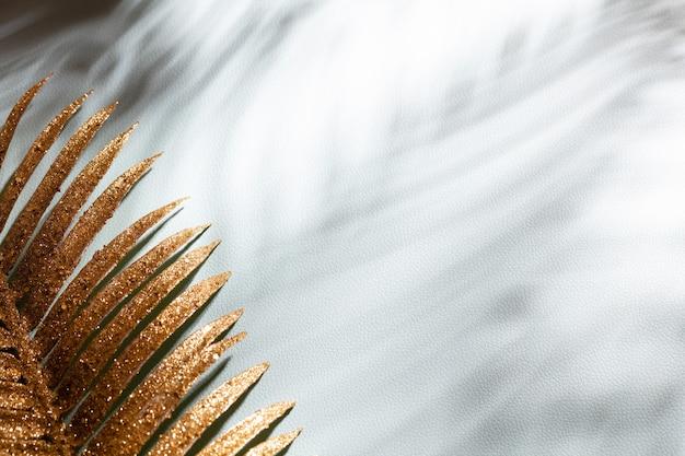 골드 팜 나뭇잎과 파란색 벽 배경에 그림자