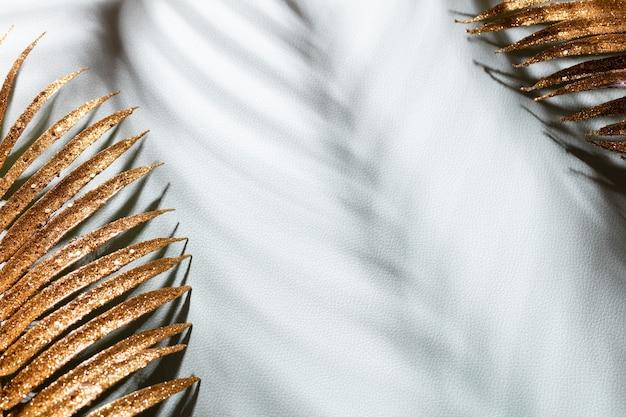 Золотые пальмовые листья и тени на синем фоне стены.