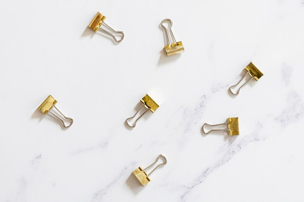 Gold paper clips on plain background