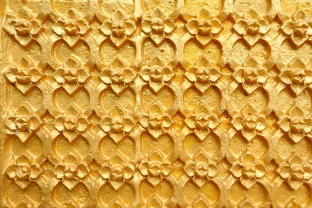 Gold patterned thai art on wall in temple