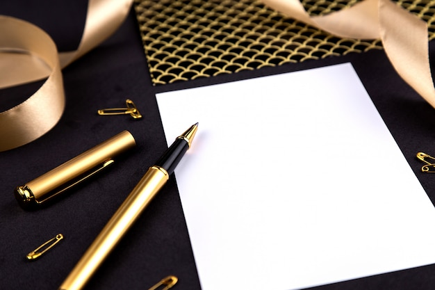 Gold pen, ribbon, paper clips and stationery on a black background with a white sheet of paper with copy space
