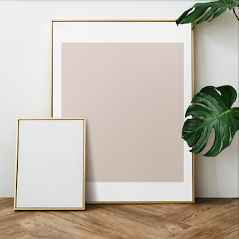 Gold photo frame by the houseplant on a wooden floor