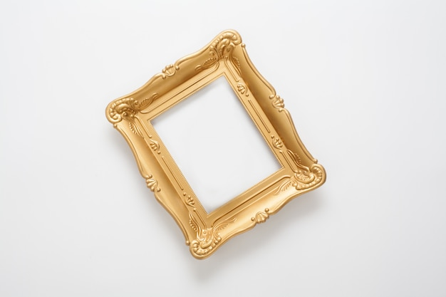 Gold photo frame in vintage style, located on a white wall. a conceptual frame for registration of certificates, awards and diplomas, or a stylish design of any subject.