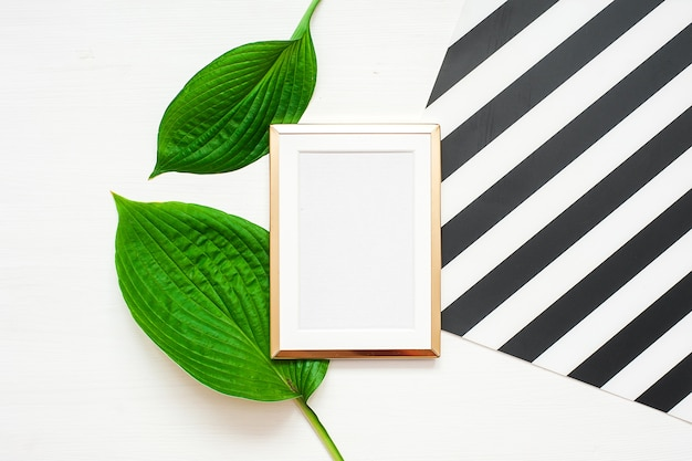 Gold photo frame with tropical leaves on black and white striped background. mock up frame