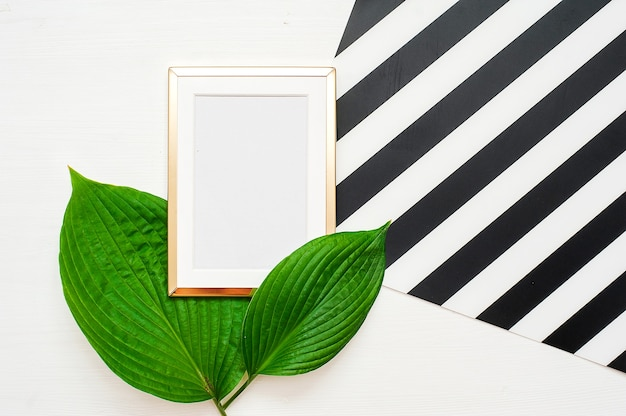 Gold photo frame with tropical leaves on black and white striped background.