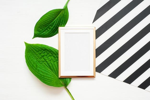 Золотая рамка с тропическими листьями на черно-белом полосатом фоне. макет кадра