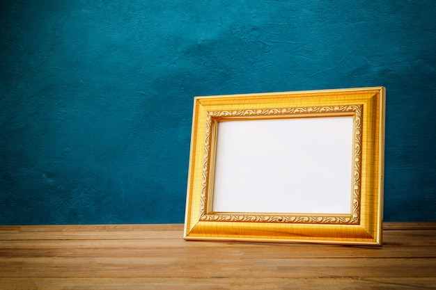 Gold photo frame on wooden