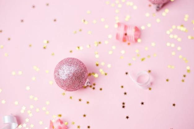 Золотые розовые и белые рождественские украшения на розовом фоне. рождество новый год или вечеринка баннер