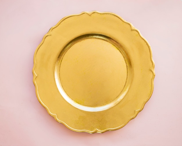 Gold plate on pink table