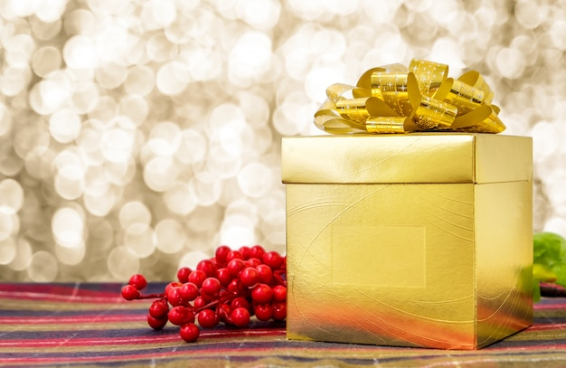 Gold present box with ribbon on table with sparkling gold bokeh light background