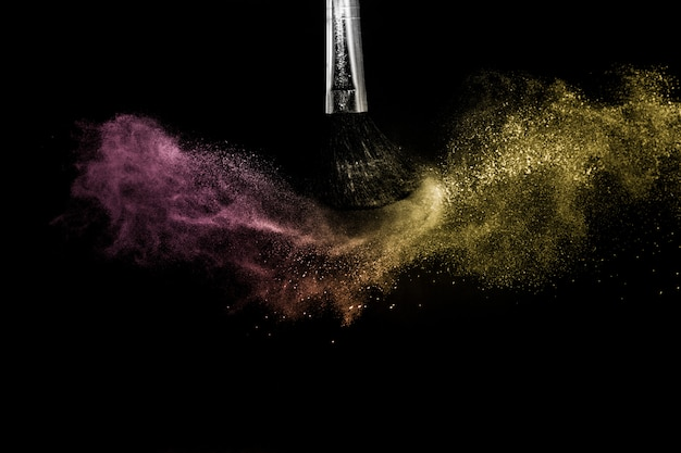Gold and purple powder splash in black background