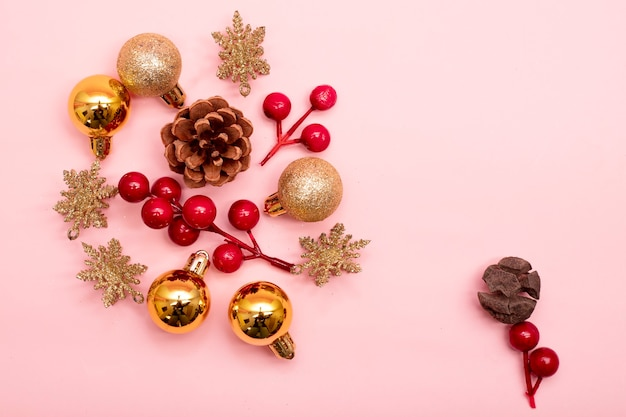 Gold and red christmas ornaments on a pink background