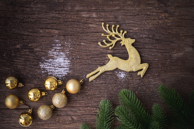 Gold reindeer with bauble on wooden table, christmas decorations background.