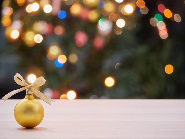 Рождественский бал с золотой лентой, связанной бабочкой, с размытой украшенной елкой и огнями боке в фоновом режиме. место для текста
