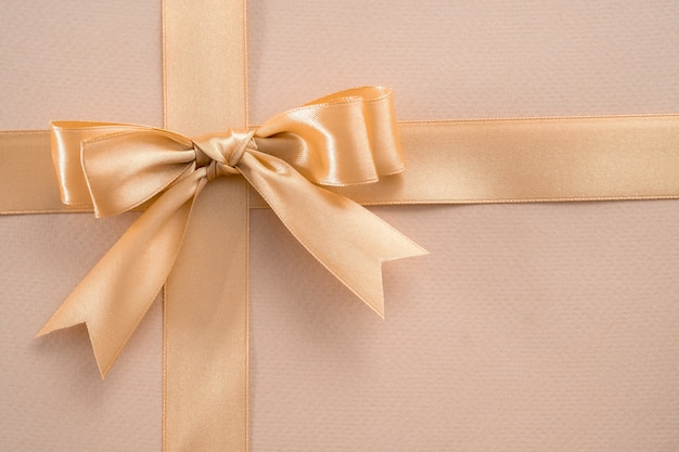 Gold ribbon with bow on golden background