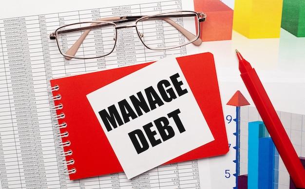 金で縁取られた眼鏡、赤いペン、カラーテーブル、白いカードが付いた赤いノートブック。デスクトップに「managedebt」というテキストが表示されます。