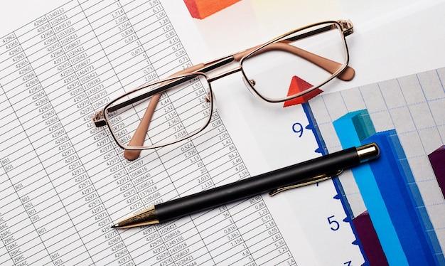 金縁のメガネ、黒いハンドル、デスクトップ上の色付きの図。
