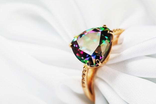 Золотое кольцо, украшенное большим переливающимся разными цветами драгоценными камнями на белой шелковой ткани.