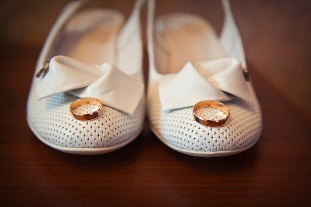 Gold ring on the bride's white shoes closeup
