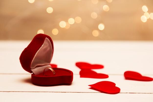 Золотое кольцо, обручальное кольцо в красной коробке и красное сердце на бело-красном фоне с красивым боке