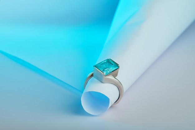 Gold ring with blue topaz on a white background