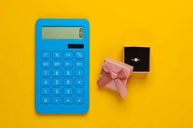 ギフトボックスにダイヤモンドが入ったゴールドリングと黄色の電卓