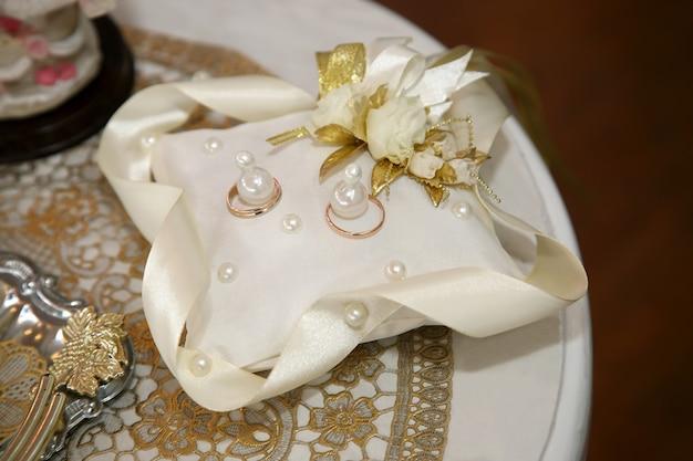 결혼식을위한 금 반지는 장식용 베개에 있습니다.
