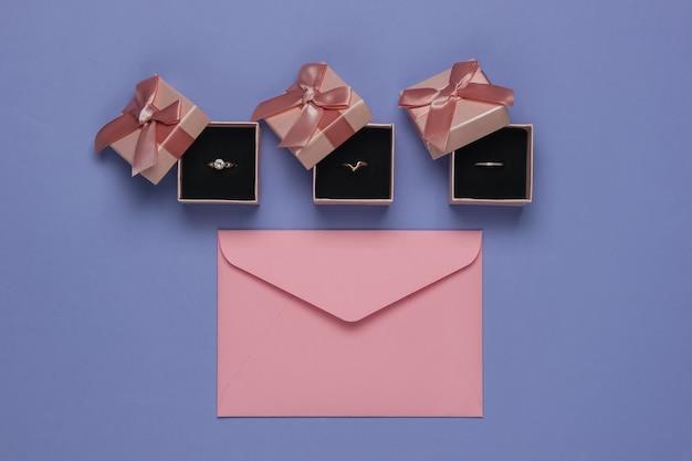 ギフトボックスの金の指輪、紫色の背景に結婚式の招待状の封筒。上面図。フラットレイ