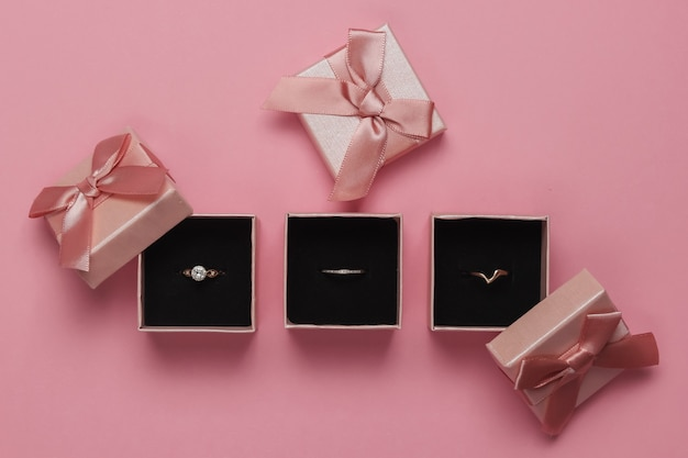 ピンクのパステルカラーの背景にギフトボックスのゴールドリング。宝石店。上面図