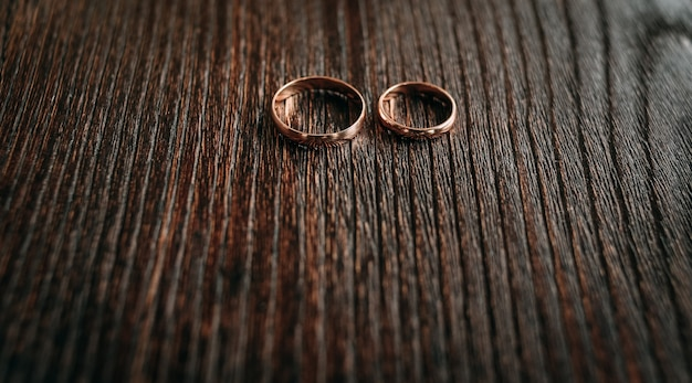 Золотые кольца на фоне wodden