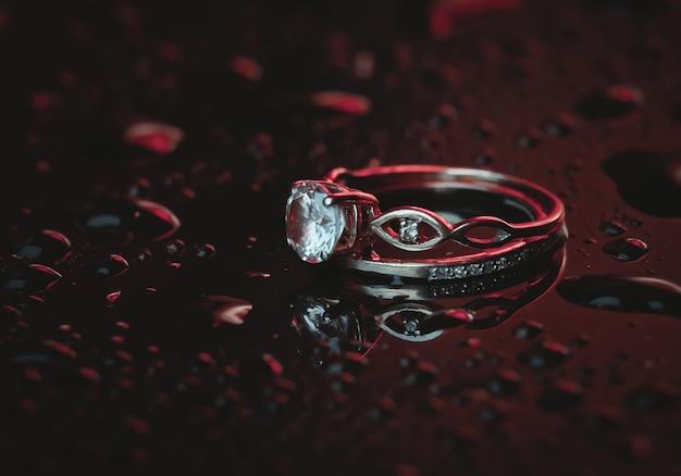 水滴のある暗闇の中で青みがかったネオンの光の中でダイヤモンドが付いた金の指輪