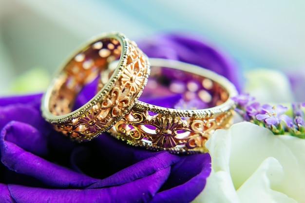 Золотые кольца с размытым фоном из белых и синих цветов