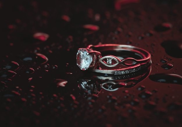 Gold rings with a diamond in bluered neon light on a dark with drops of water