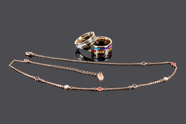 Gold rings with enamel and golden chain on dark reflective surface