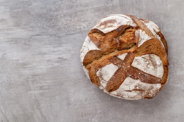 木製の背景にパンとパンの金の素朴な無愛想なパン。平面図の上から捉えた静物、フラットレイ。